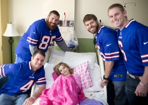 Buffalo Bills players visit a patient on behalf of the P.U.N.T. Foundation.